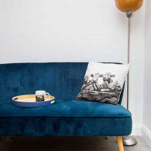 Grey cow print cushion displayed on a navy sofa in a sitting room set up