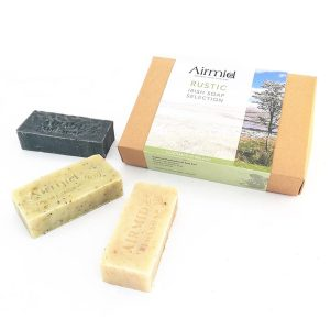 airmid soap rustic collection package and three soap bars laid out on a white background