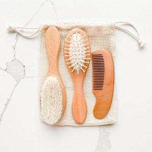 Sustainable wooden baby hairbrushes and comb laid on a cotton mesh bag against a white marbled background
