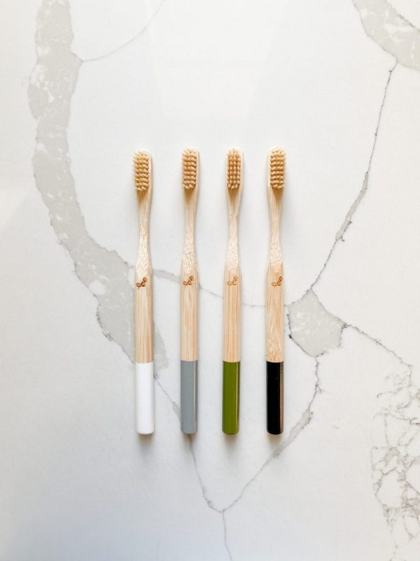 four bamboo toothbrushes laid flat on a marble background