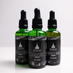 Three 50ml green beard oil bottoms with black packaging against white background