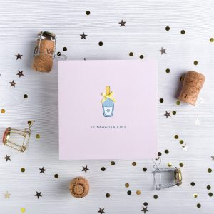 Congratulations card with a champagne bottle drawing and gold bow finishing. Plain background with decorative pieces including champagne corks and sparkle