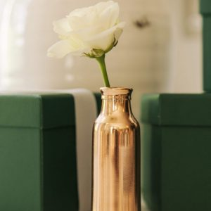 Aesthetic copper bud vase with a white rose with soft out of focus green gift boxes in background