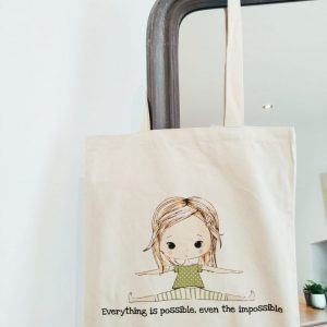 The organic cotton daisy cote with the phrase everything is possible, even the impossible