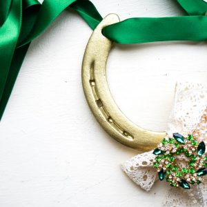 Gold horseshoe with classy broach and pearl decorated with emerald silk ribbon