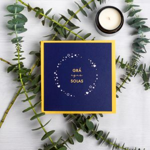 Navy grá agus solas card with star detailing laid on a yellow envelope with plant stems and a candle on a light background