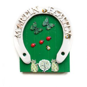 Bright green Irish wooden fairy door with ladybirds and butterflies and family name on white horseshoe