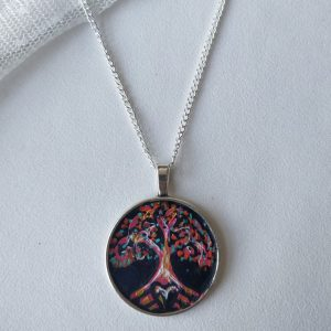 Handpainted tree of life necklace on silver chain laid on white background