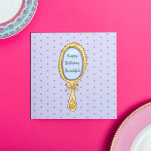 Grey card with purple polka dots and a gold mirror saying happy birthday beautiful on a pink background