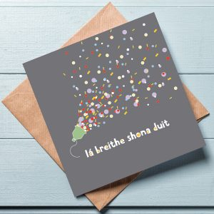 Grey Happy Birthday Card laid flat on top of a brown envelope against a blue-grey background
