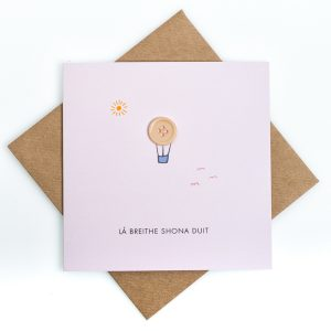 Card with a hot air balloon simple sky design and button detailing saying lá breithe shona duit and a brown envelope against a white background