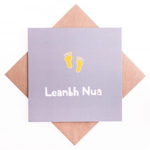 Grey new baby card with yellow baby feet design laid on a brown envelope against a white background