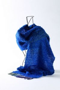 Aesthetic photo of handwoven blue scarf draped for display