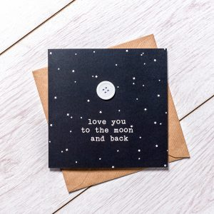 Black card with white dots and a white button detail saying love you to the moon and back laid on a brown envelope on a plain light background