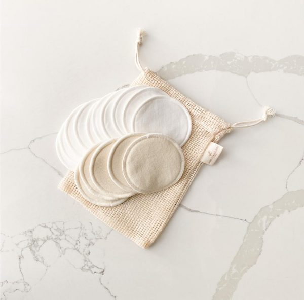 Cotton mesh bag and cotton reusable makeup remover pads laid on a marble background