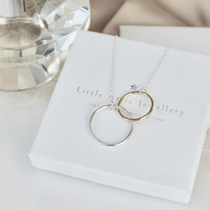 Sterling silver and 9ct rose gold looped necklace on elegant white box and diamond silk background