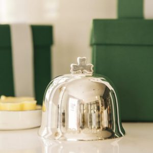 Silver butter dish on table with shamrock detail and soft out of focus green gift boxes in background