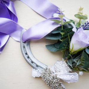 Silver horseshoe decorated with purple flowers and a sparkly broach and purple ribbon.