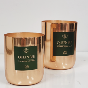 Two queen bee scented candles in copper vessels with a plain light background
