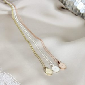 Three round pendant in gold, rose gold, and sterling silver necklaces laid on silk