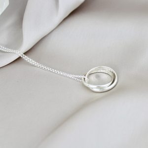 Sterling silver russian wedding ring neclace laid on silk