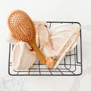 Metal basket containing sustainable selfcare items on a neutral light background