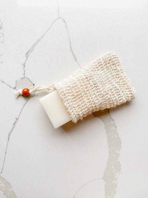 Sustainable white sisal soap bag with bar of soap laid on a marble background