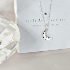 sterling silver moon necklace displayed on white packaging beside big diamond