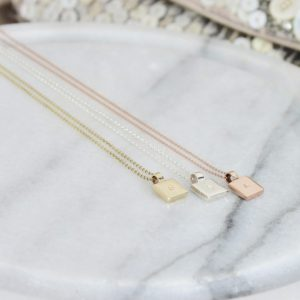 Three square pendant necklaces laid on marble platter aesthetic