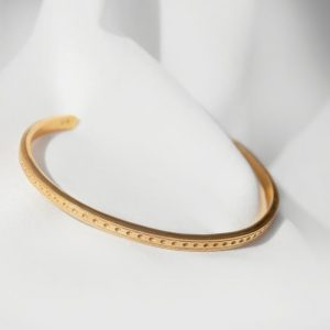 Gold open bangle laid on white silk background