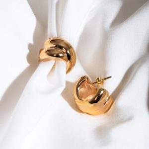 Chic gold hoop earrings laid on white silk background