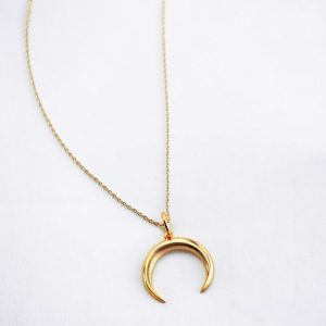 Gold crescent moon necklace on white background