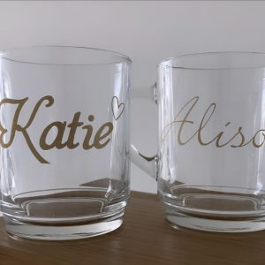 Pair of glass mugs on a table personalised with the names Katie and Alison in gold.