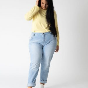 Model wearing denim jeans and a yellow top.