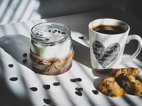 Candle in glass jar decorated with coffee beans and coffee cup