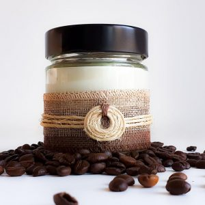 White soy candle in glass jar surrounded by coffee beans
