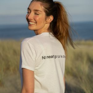 Woman wearing white tshirt with gaeilge writing on the back and a beach in the background