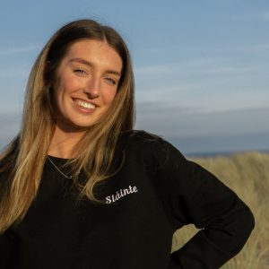 Woman wearing black crew neck and a beach in the background