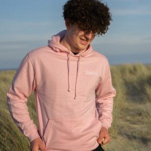 Man wearing pink hoodie with a beach in the background