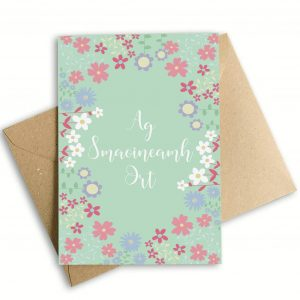 thinking of you card as Gaeilige with a blue background and pink flowers