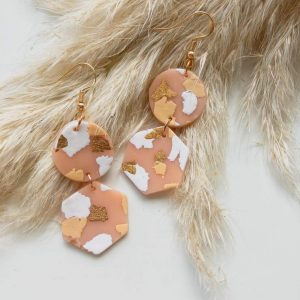 Earrings laying on some pale feathers.
