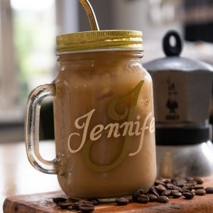 Drinking glass jam jar filled with coffee with a metal straw.