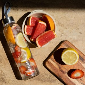 Clear water bottle filled with water and fruit, next to grapefruit.