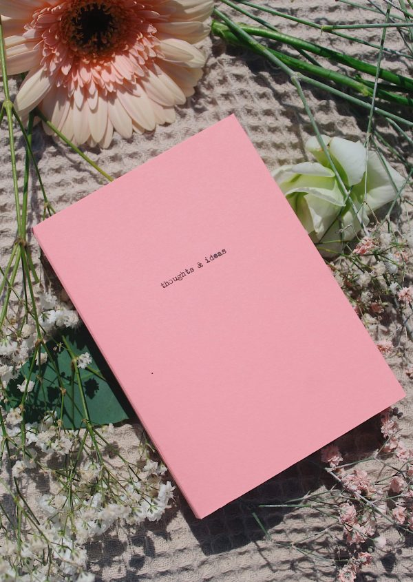 Pink A6 notebook laying on flowers.