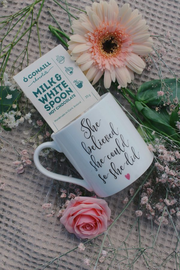 White china mug with the words 'she believed she could so she did' written on the front, with a milk chocolate spoon inside it.