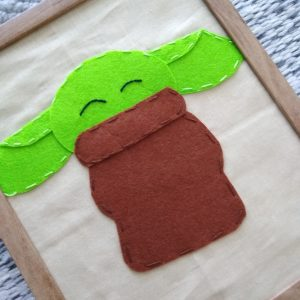 Baby Yoda sewing kit with a wooden frame.