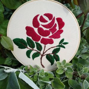 Embroidery flower rose canvas sitting on a plant.